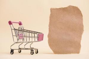 Carrito de la compra en miniatura vacío cerca de un trozo de papel rasgado contra el telón de fondo de color foto