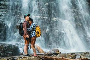 Man and woman hikers trekking a rocky path against the background of a waterfall and rocks photo