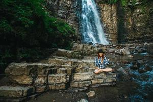 Woman with red hair in a hat and shirt meditating on rocks in a lotus position against a waterfall photo