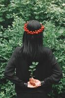 Beautiful girl with black hair and red accessories that holds a twig in her arms behind her back against the background of the forest photo
