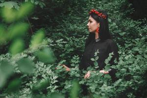 hermosa chica en vestido negro y adornos rojos el fondo del bosque. espacio para su mensaje de texto o contenido promocional foto