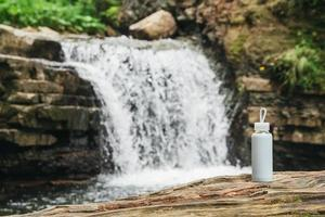 White bottle with water standing on a wooden trunk against the background of a river and a waterfall. The concept of pure natural drinking water photo
