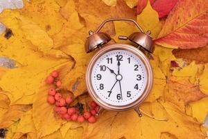 Autumn fall leaves and alarm clock. Autumn time concept photo