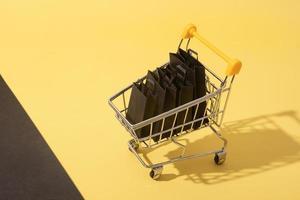 Carro de supermercado en miniatura con bolsas de la compra en venta de viernes negro sobre fondo amarillo foto