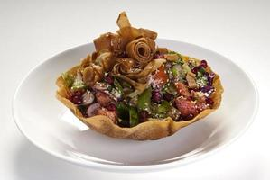 Delicious Fattoush or Arab salad with pita croutons, fresh vegetables and herbs, on white plate. Middle Eastern bread salad. Easy and healthy authentic recipe. photo