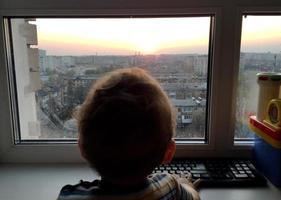 Beautiful baby boy with child face posing photographer near window photo