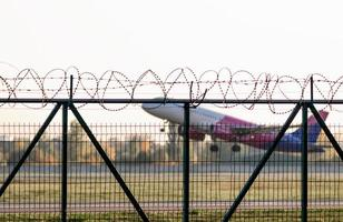 Kiev, Ukraine, 2021 - Airplane taking off behind a fence photo