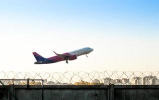 Kiev, Ukraine, 2021 - Airplane taking off over a fence with barbed wire photo