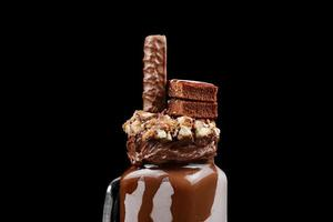 Chocolate extreme milkshake with brownie cake, chocolate paste and sweets. Crazy freakshake food trend. Copy space photo