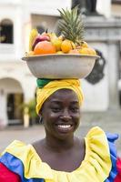 CARTAGENA, COLOMBIA, SEPTEMBER 16, 2019 - Unidentified palenquera, fruit seller lady on the street of Cartagena. These Afro-Colombian women come from village San Basilio de Palenque, outside the city. photo