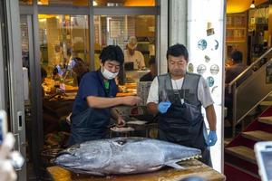 TOKYO, JAPAN, OCTOBER 2, 2016 - Unidentified people at Tsukiji fish market in Tokyo, Japan. Tsukiji is the biggest wholesale fish and seafood market in the world. photo