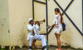 HAVANA, CUBA, JULY 4, 2017 - Unidentified man playing trumpet on the street of Havana, Cuba. Street musicians are common in Havana where they play music for tourists. photo