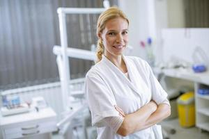 Attractive female dentist posing in modern dental office photo