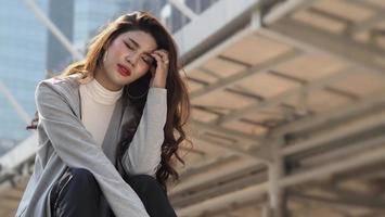 Lay off. Sacked. Fired business woman sitting on stairs of office building outside. photo