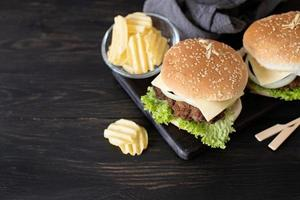 A set of homemade delicious burgers of beef, onion, cheese and lettuce on a dark wooden background photo