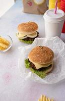 Set of homemade burgers, chips and drink photo