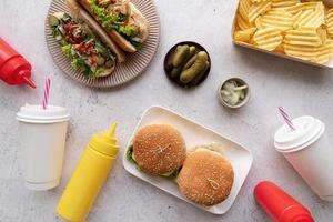 Top view of fast food, hotdogs, chips, burgers and drinks photo