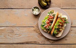 Hot dog with sausage, letuce, cucumber and onion on beige plate on wooden background photo