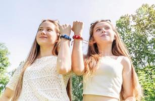 Amigos felices mostrando sus pulseras de la amistad al aire libre foto