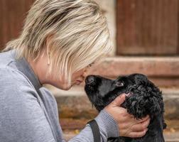 Joven mujer rubia tocando su nariz de perro fuera foto