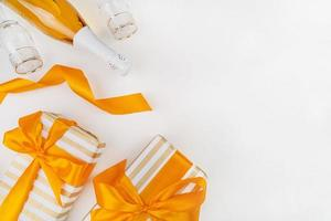 Christmas gifts wrapped with gold and white paper, champagne and glasses top view flat lay photo