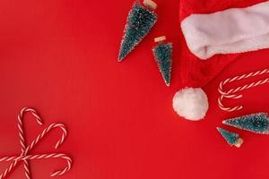 Christmas decorations candy canes, fir trees and sants hat top view on red background photo