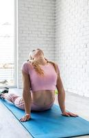 Athletic woman stretching on a fitness mat at home at white brick wall background photo