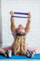 Athletic woman doing exercises using a resistance band on a fitness mat at home at white brick wall background photo