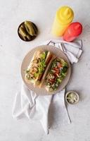 Hot dog with sausage, letuce, cucumber and onion on beige plate on concrete background photo