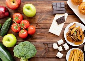 Healthy and unhealthy food concept. Fruit and vegetables vs sweets and potatoe fries top view flat lay on wooden background photo