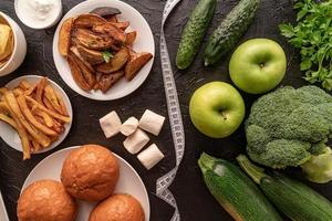 Fruit and vegetables vs sweets and potato fries top view flat lay photo