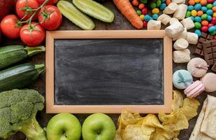Fruit and vegetables vs sweets and potato fries around the blank chalk board top view flat lay photo