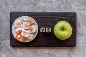 sweets versus apple top view on dark background photo