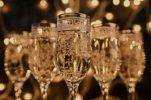 glasses of champagne on dark background with lights photo