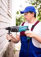 Construction worker in protection glasses and uniform with perforator drilling the wall outdoors. Man with drill photo