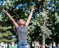 Happy caucasian woman in casual clothes smiling and having fun in the park in summer sunny day photo