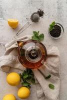 teapot with black tea decorated with mint leaves, lemons and dry tea leaves top view flat lay photo