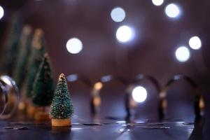 Christmas tree decorations standing in the line with fairy lights background with copy space photo