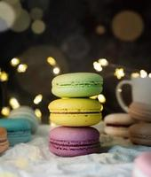 stack of macaroons on the table, fairy lights and bokeh background photo