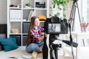 Mujer haciendo un video para su blog sobre arte usando una cámara digital montada en un trípode foto