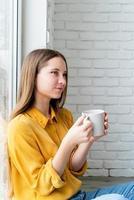 Attractive woman drinking tea sitting at the floor photo