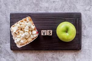 pop corn versus apple top view on dark background photo
