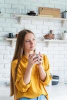 Attractive woman drinking tea in her kitchen photo