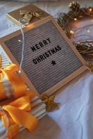 Felt letter board Merry Christmas on the bed decorated with golden wreath, lights and gift boxes photo