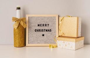 Felt letter board Merry Christmas decorated with golden champagne bottle and gift boxes photo
