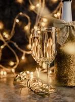 two champagne flute with shiny bottle on dark background with lights photo