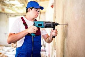 Construction worker in protection glasses and uniform with perforator drilling the wall indoors. Man with drill photo