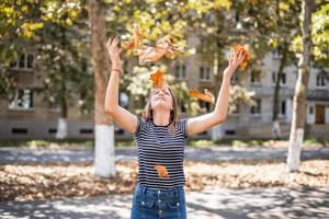 young pretty caucasian woman throwing autumn leaves up on urban park background photo