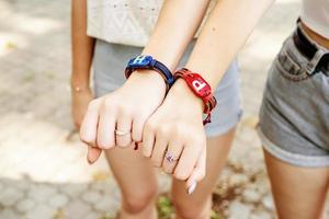 Dos amigas mostrando las manos con pulseras de la amistad foto