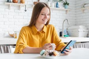 Attractive teenager woman in yellow shirt drinking tea photo